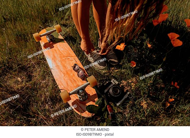 Young female skateboarder tying shoelaces in grass, Jalama, California, USA