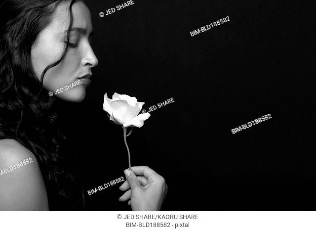 Hispanic woman smelling rose
