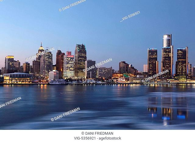 Skyline of downtown Detroit, Michigan, USA. Ice can be seen floating on the Detroit River as the buildings are illuminated at dusk