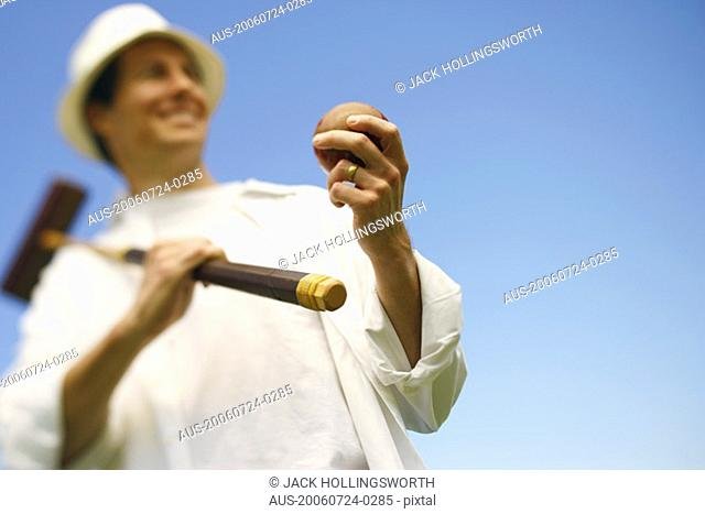 Low angle view of a mid adult man holding a croquet mallet and a ball