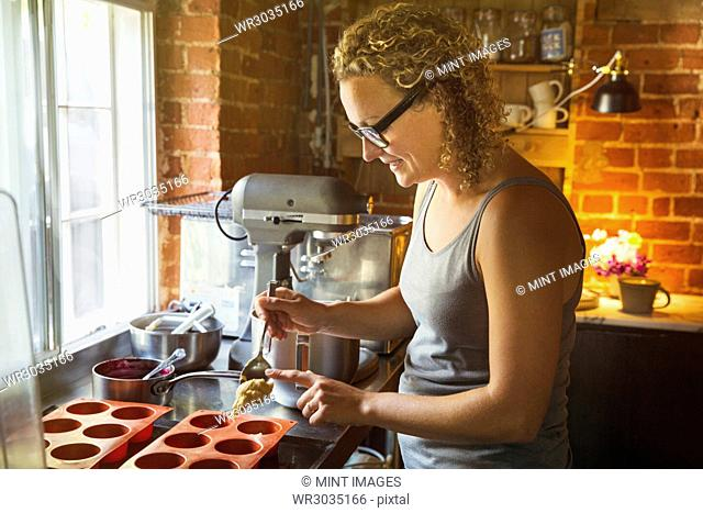Side view of woman standing in a kitchen, baking, filling silicone molds
