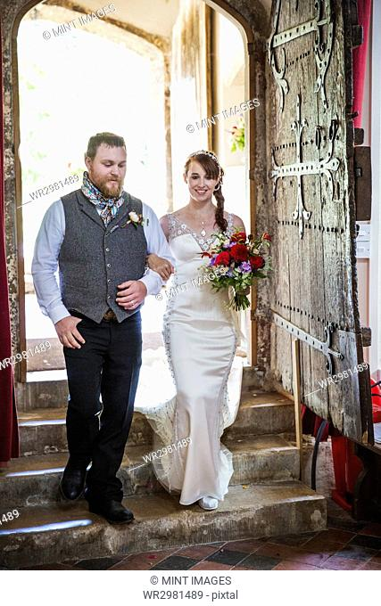 Smiling bride and groom entering church