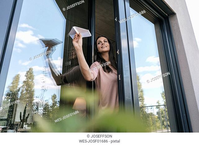 Woman holding paper plane at the window