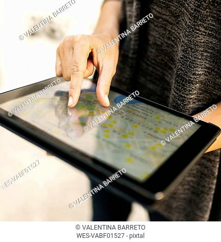 Close-up of woman using tablet with digital street map