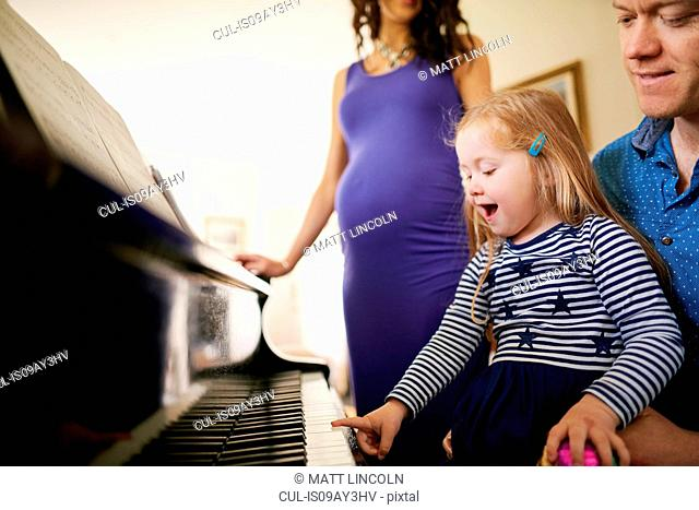 Parents teaching daughter to play piano