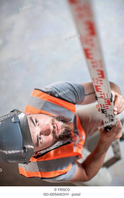 High angle view of young male builder measuring with ruler