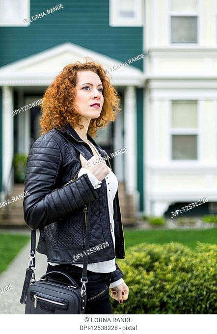 A woman with red, curly hair walking outdoors in a neighbourhood; North Vancouver, British Columbia, Canada