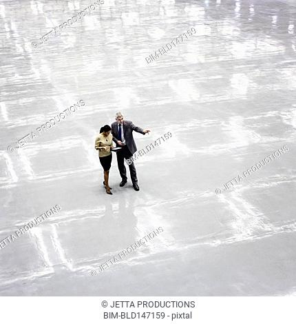 Business people talking in empty convention center