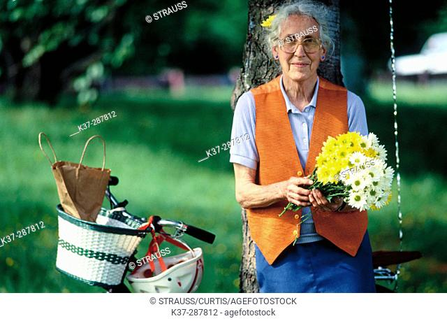 Senior woman with bike in park