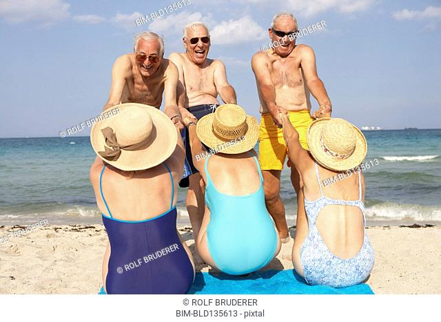 Senior couples playing on beach