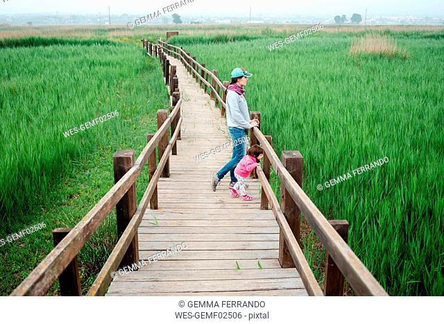 Mother and daughter on a wooden walkway, looking at rice fields