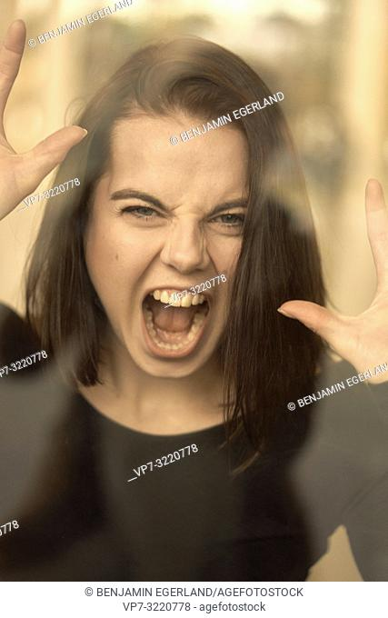 portrait of woman screaming behind glass window, furious angry emotion, feeling expelled, mental health, in Munich, Germany