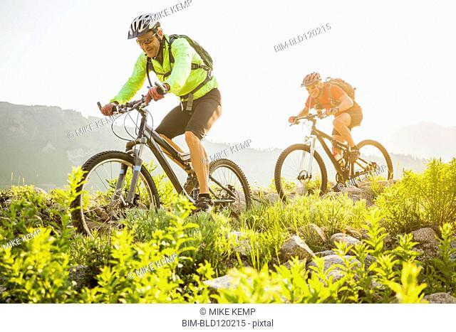 Caucasian men riding mountain bikes on trail