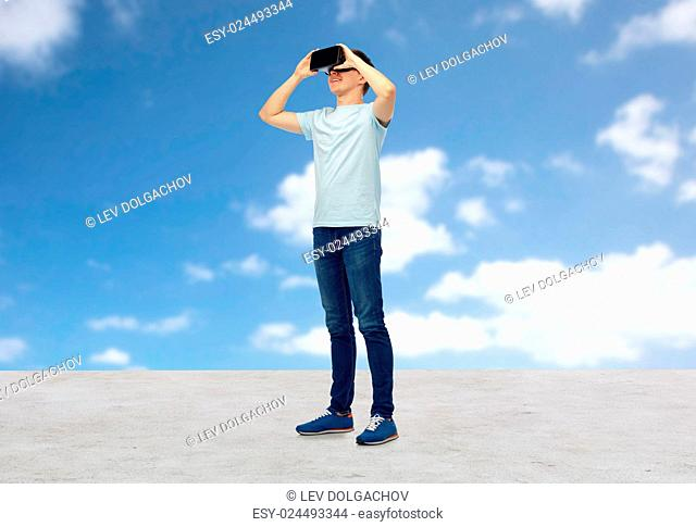 3d technology, virtual reality, entertainment, cyberspace and people concept - happy young man with virtual reality headset or 3d glasses looking at something...