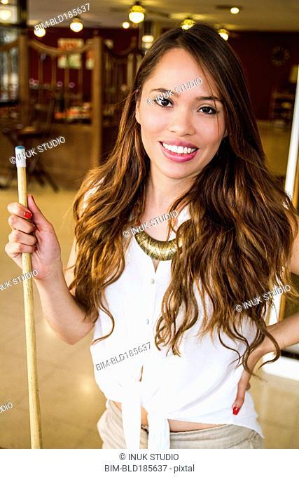 Hispanic woman holding pool cue