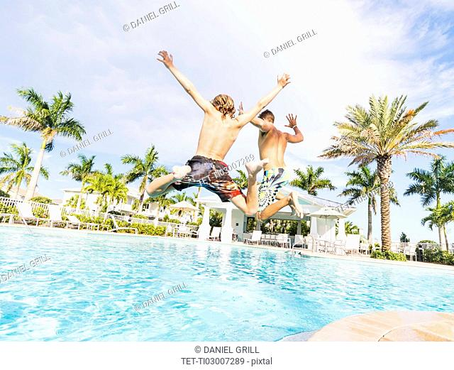 Boy (8-9) diving into swimming pool with his brother