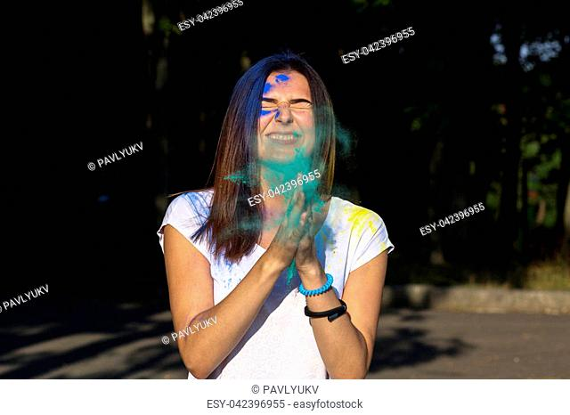Closeup portrait of happy young girl posing with exploding green Holi powder in the park
