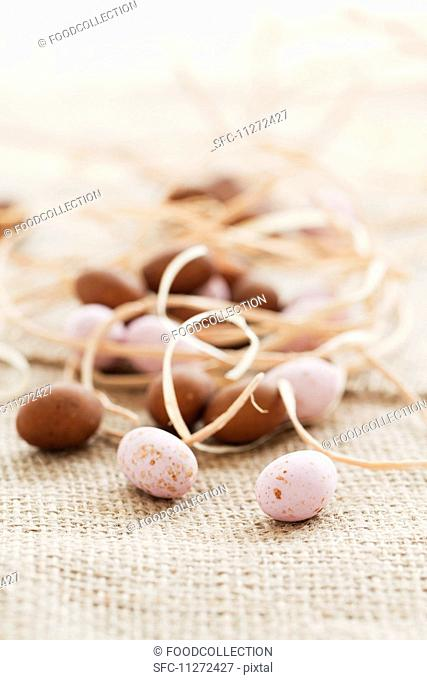 Pink and brown mini chocolate eggs with straw on a piece of jute
