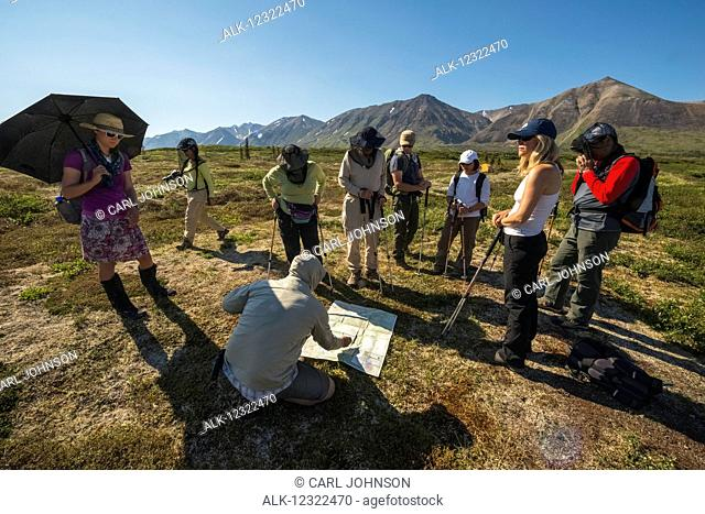 A group of hikers prepare for a day hike in the backcountry near Twin Lakes in Lake Clark National Park & Preserve, Southcentral Alaska, USA