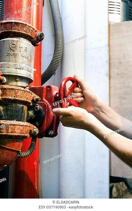 The hands of an adult man in the action of turning a bright red valve, part of an industrial plumbing system