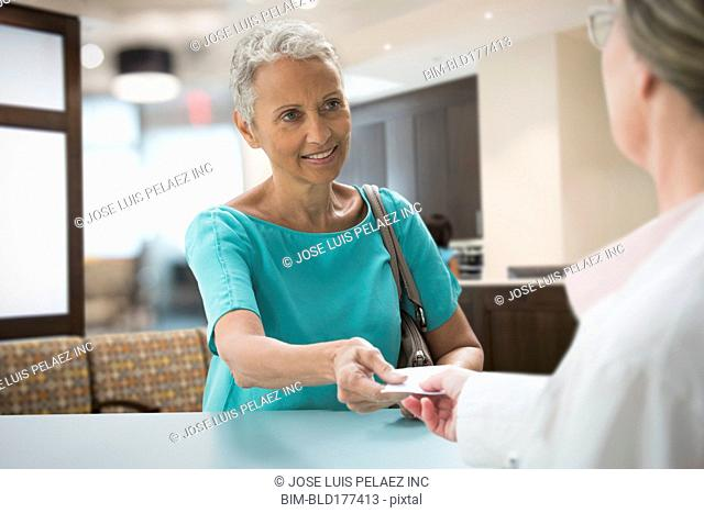 Woman passing insurance card in hospital