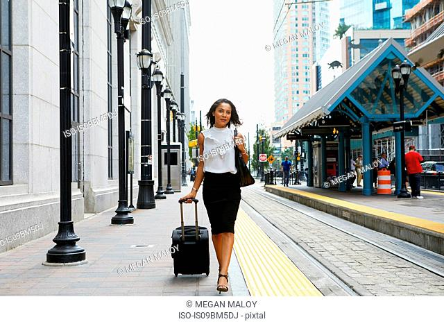 Businesswoman pulling luggage alongside train