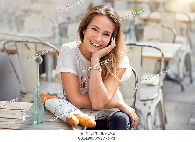 Young woman sitting at pavement cafe with baguettes, hand on chin looking at camera smiling