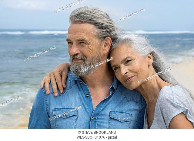 Handsome senior couple embracing at the beach