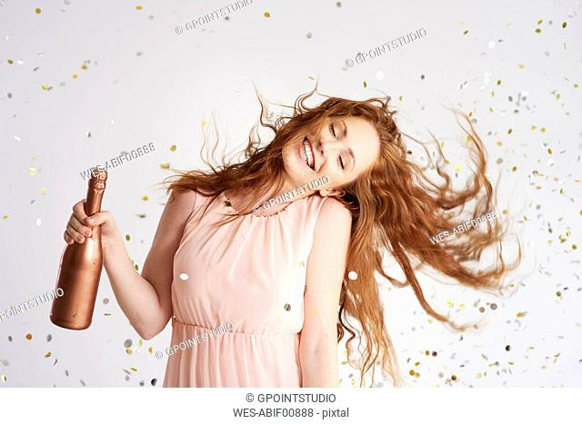 Portrait of happy young woman dancing with bottle of champagne