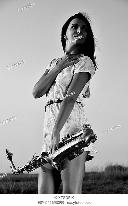 Beautiful girl holding a saxophone in his hands