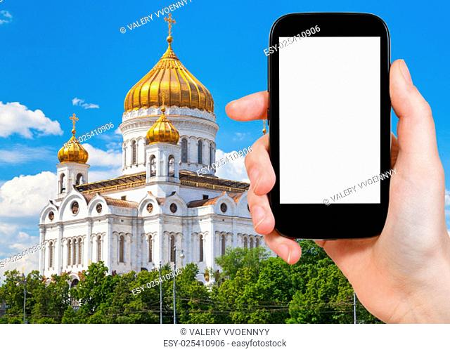 travel concept - tourist photograph Cathedral of Christ the Saviour, Moscow, Russia on smartphone with cut out screen with blank place for advertising logo