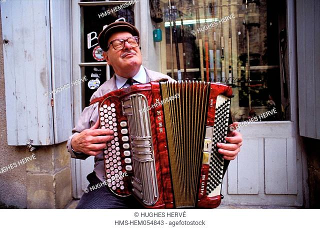 France, Dordogne, Perigord Noir, Sarlat, Jacky Porret and his accordion in front of his fishing bar