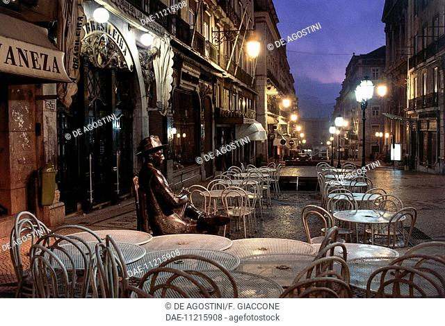 Statue of Fernando Pessoa (Lisbon, 1888-1935), Portuguese poet and writer, sitting at a table at Cafe Brasileira, 1988, night view, Chiado district, Lisbon