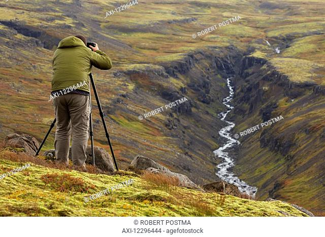 Man photographing a river valley in Iceland during autumn; Iceland