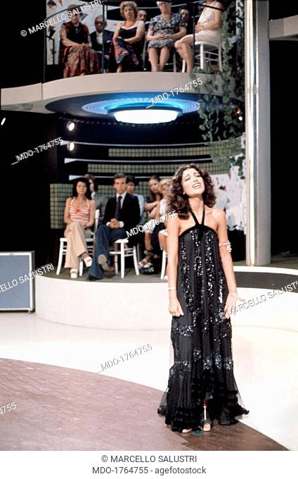 Mia Martini singing a song in a long dress. Italian singer Mia Martini (Domenica Berté) singing a song wearing a long black dress trimmed with rhinestones