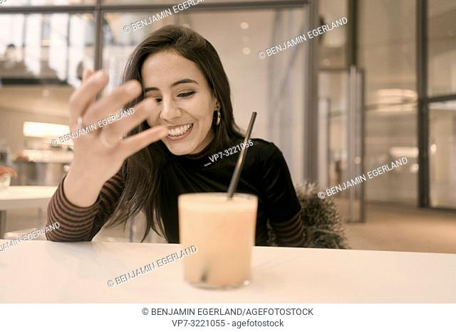 portrait of happy woman with healthy juice glass enjoying break at table in café, candid emotional expression, in Munich, Germany