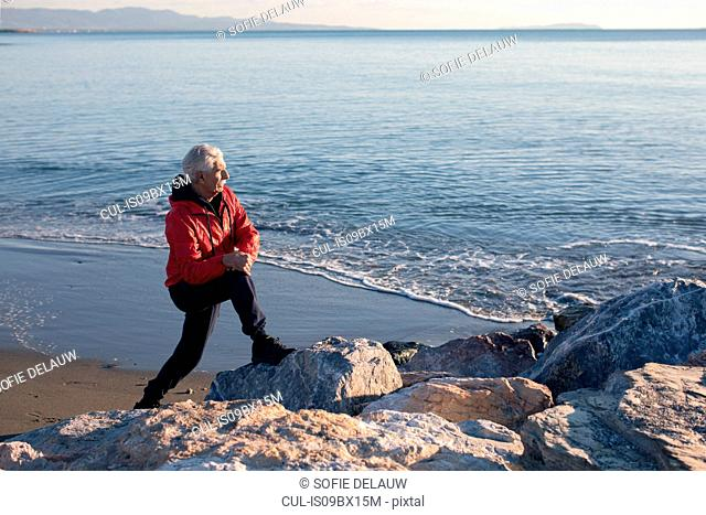 Senior man doing stretching exercises on beach, Livorno, Italy
