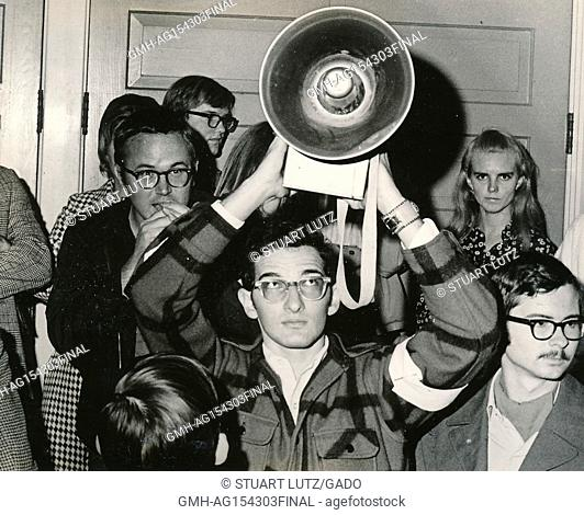 A student wearing hippie attire holds a bullhorn loudspeaker above his head while another student speaks into the microphone during an anti Vietnam War student...