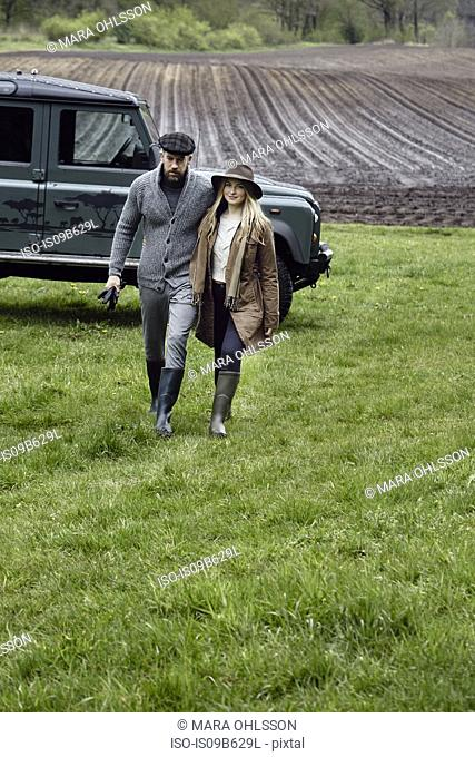 Country couple in outdoor clothes walking up field
