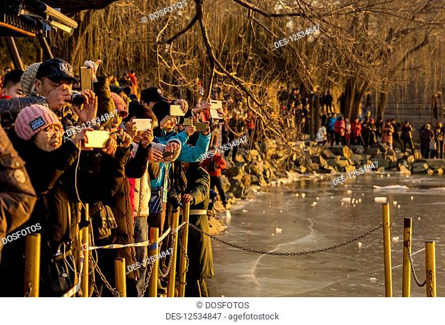 Crowd of tourists taking photographs of the 17 Arch Bridge at sunset, standing at the edge of frozen Kunming Lake, The Summer Palace; Beijing, China