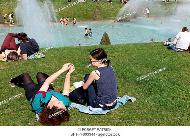 TOURISTS ON THE LAWN IN FRONT OF THE FOUNTAIN PONDS OF THE TROCADERO GARDEN IN FRONT OF THE EIFFEL TOWER, 16TH ARRONDISSEMENT, PARIS (75), FRANCE