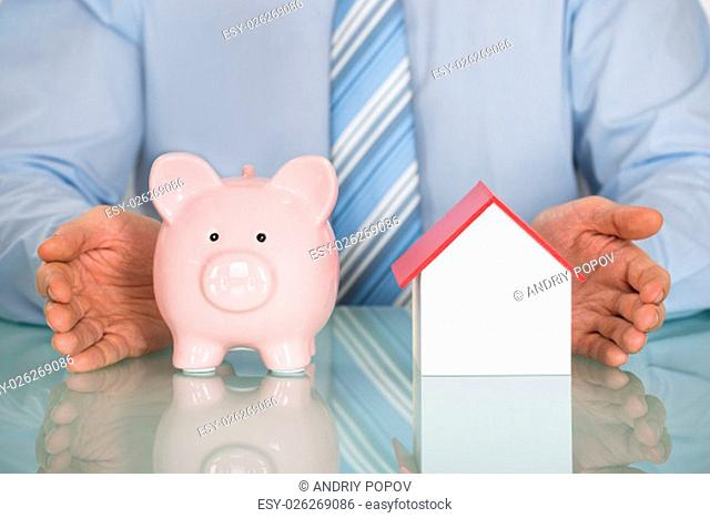 Close-up Of Businessman Protecting Piggy Bank And House Model