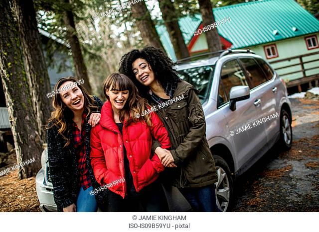 Portrait of three friends standing beside car, laughing
