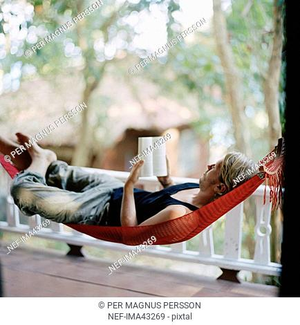 A young man in a hammock reading a book Thailand
