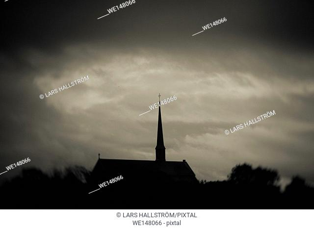 Dark and moody sky with silhouette of medieval church. Vadstena Abbey, Sweden