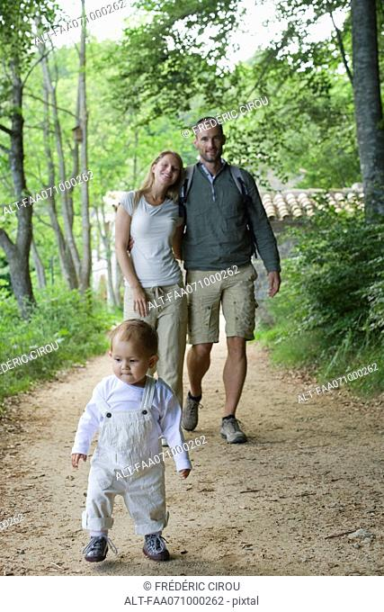Toddler girl walking in woods with parents
