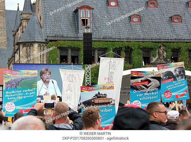 Demonstrators hold up signs of the Alternative fuer Deutschland (AfD) party during an election campaign event of the CDU'party with chancellor Angela Merkel on...