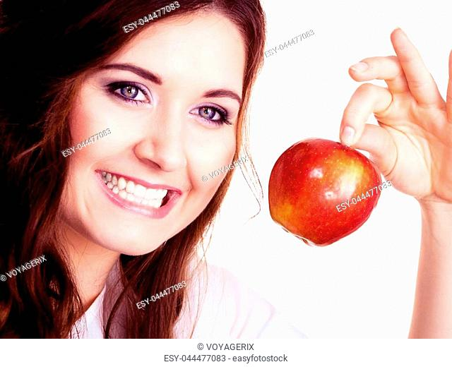 Woman holding red apple fruit in hand close to face, smiling, isolated on white. Healthy eating, high fibre diet concept