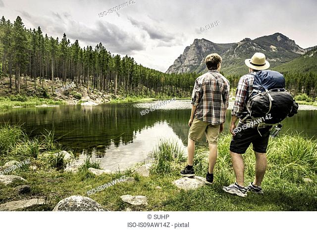 Rear view of father and son looking at view of mountain over Greenough lake, Red Lodge, Montana, USA