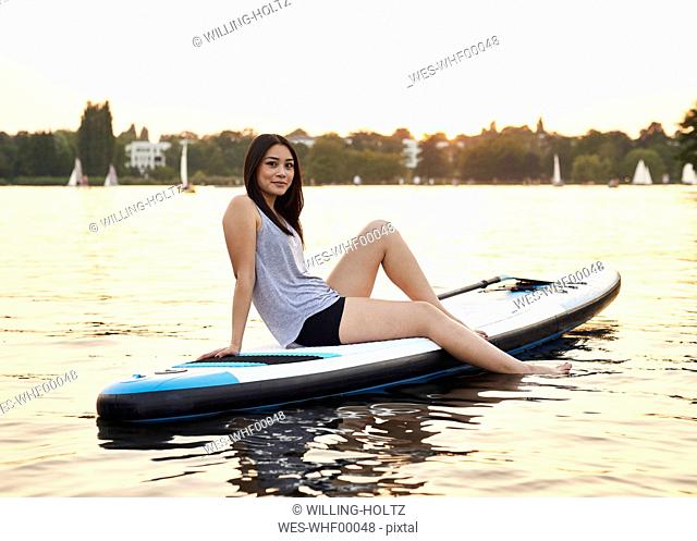 Germany, Hamburg, Young woman on paddleboard enjoying summer